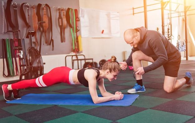 Jeune femme en tenue de sport faisant planche d'exercice avec un instructeur masculin note le temps sur un chronomètre. exercice d'endurance au gymnase