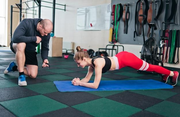 Jeune femme en tenue de sport faisant planche d'exercice avec un instructeur masculin note le temps sur un chronomètre. exercice d'endurance dans la salle de sport