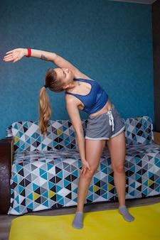 Une jeune femme en tenue de sport noire pratique le yoga, se tient debout dans la pose de coude avant, exécute un exercice, une fille athlétique fait de l'exercice à la maison ou dans un studio de yoga aux murs gris, étirement du corps