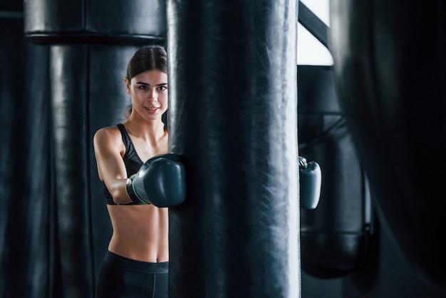 Une jeune femme en tenue sportive est dans la salle de gym en train de faire de l'exercice. conception de la boxe.