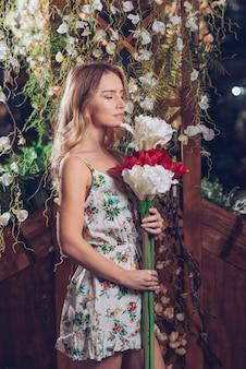 Jeune femme, tenue, tas, artificiel, blanc, rouge, fleurs, debout, dans, jardin