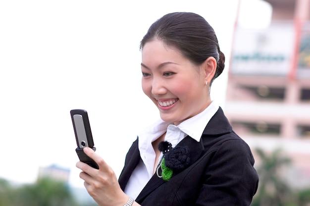 Jeune femme, tenue, téléphone portable, sourire