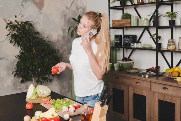 Jeune femme, tenue, tomates rouges, dans, main, parler, mobile, dans cuisine