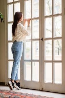 Jeune femme sur la terrasse regarde par une grande fenêtre