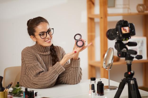 Jeune femme testant des produits de maquillage pour la vidéo
