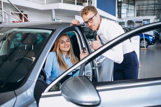 Jeune femme teste une voiture dans une salle d'exposition