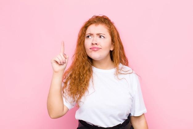Jeune femme à tête rouge se sentant comme un génie tenant fièrement le doigt en l'air après avoir réalisé une excellente idée, disant eureka sur mur rose