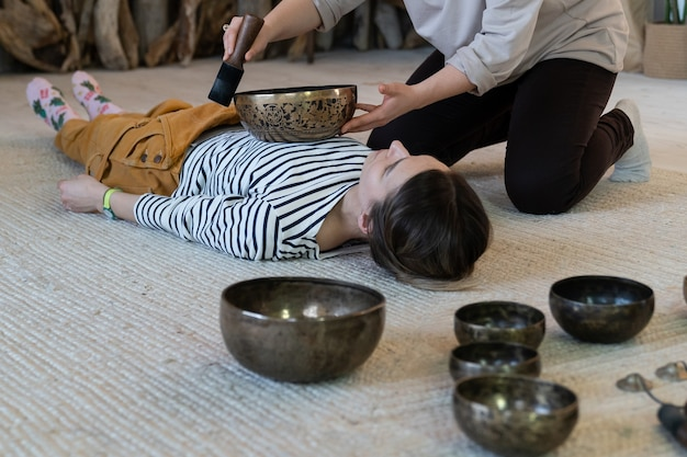 Une jeune femme a une thérapie de bol chantant de massage tibétain avec des cymbales de bronze tibétaines traditionnelles à la maison