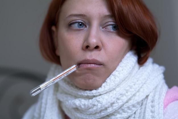 Une jeune femme avec un thermomètre
