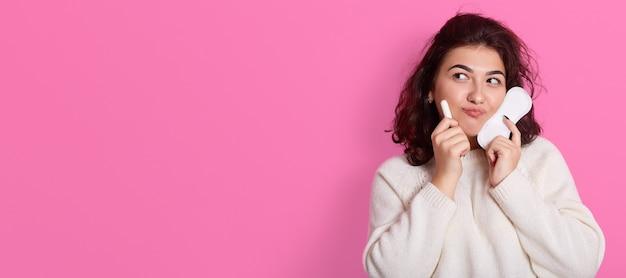 Jeune femme tient deux produits intimes, choisit entre un tampon et une serviette pendant les règles