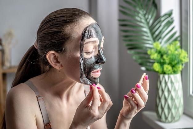 La jeune femme tient un miroir dans sa main et enlève un masque noir cosmétique de son visage