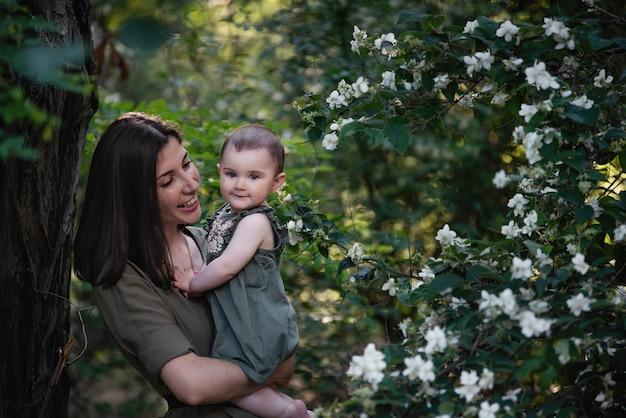 Une jeune femme tient un petit bébé dans ses bras. une belle mère se promène avec sa fille dans un parc verdoyant près des buissons de jasmin