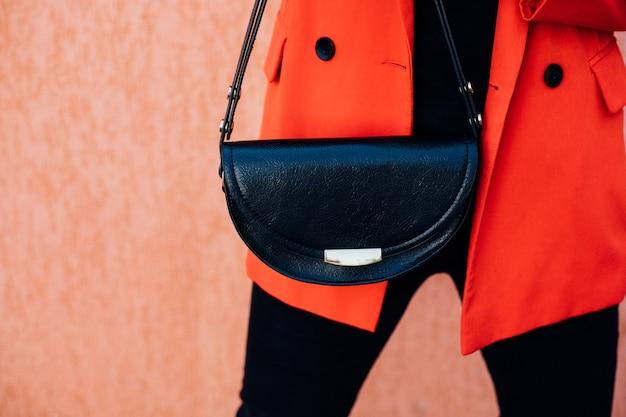 Une jeune femme tient un petit sac noir dans ses mains. une fille d'affaires élégante. une femme d'affaires en milieu urbain.