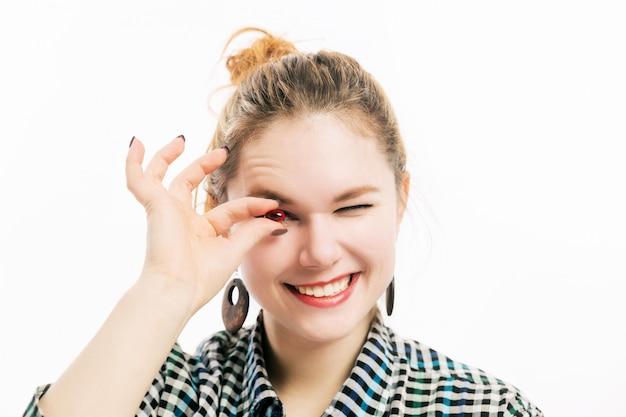 Jeune femme tient une pilule dans sa main et sourit