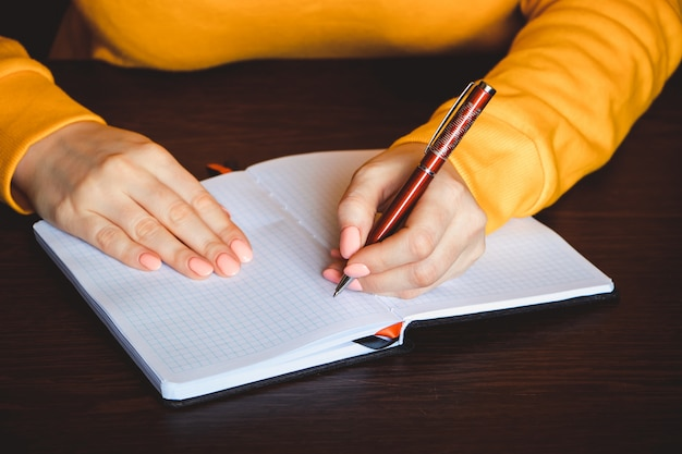 Jeune femme tient un stylo dans sa main gauche et écrit une note dans un cahier vierge. journée internationale des gauchers