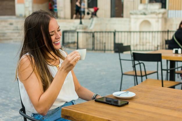 Jeune femme tient une tasse de café pendant qu'elle sourit.