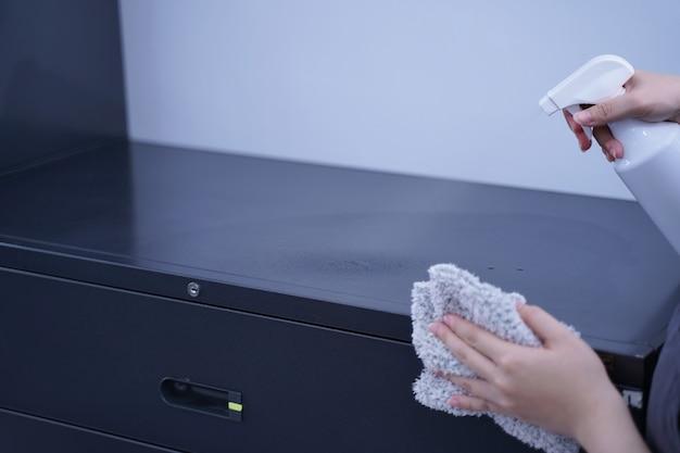 Une jeune femme tient un vaporisateur, un chiffon pour nettoyer, essuyer la surface d'hébergement de l'étagère de l'armoire métallique de bureau, gros plan, mode de vie, concept d'antibactérien.