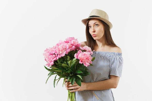 Jeune femme timide mignonne en robe bleue, chapeau tenant un bouquet de belles fleurs de pivoines roses isolées sur fond blanc. saint-valentin, concept de vacances de la journée internationale de la femme. espace publicitaire