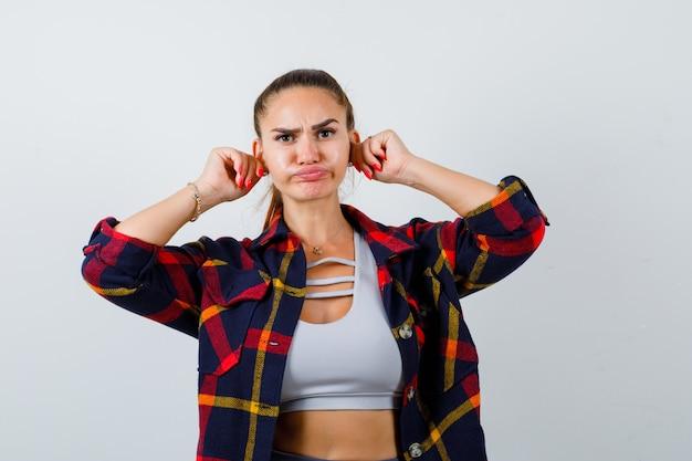 Jeune femme tirant les oreilles tout en soufflant les joues dans un haut court, une chemise à carreaux et l'air drôle. vue de face.