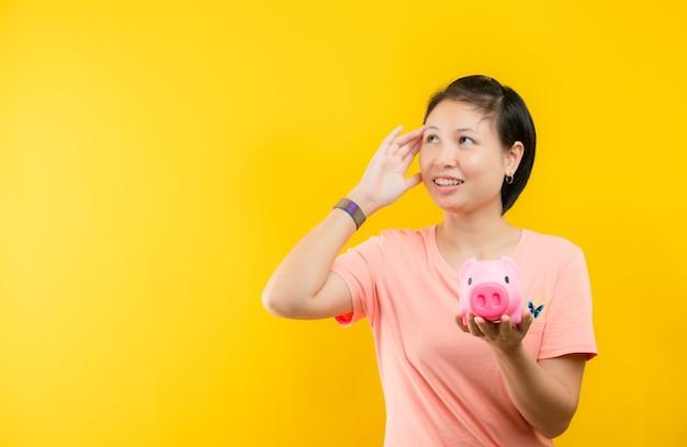 Jeune femme avec tirelire rose avec de l'argent accumulé pour faire des rêves à fond jaune.concept d'épargne.