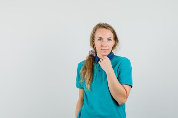 Jeune femme touchant le menton avec le poing levé en t-shirt et à la jolie