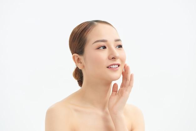 Jeune femme touchant son visage isolé sur fond blanc