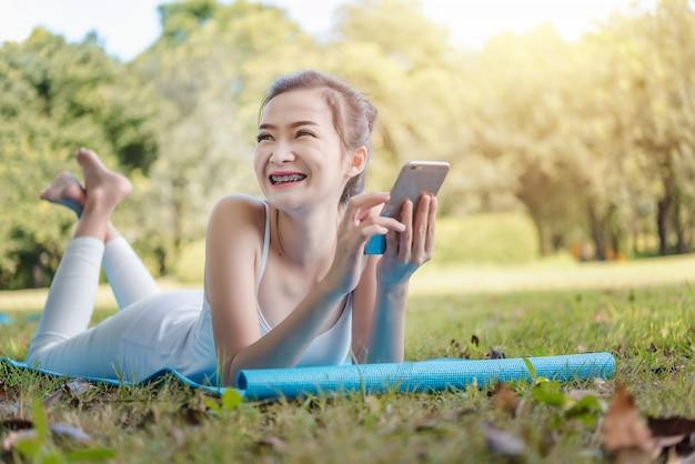 Jeune femme touchant le téléphone portable et se reposant sur une journée ensoleillée sur l'herbe.
