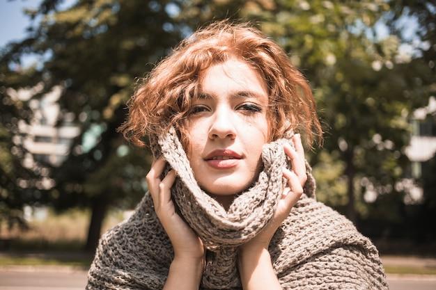 Jeune femme touchant le visage avec un foulard dans le parc