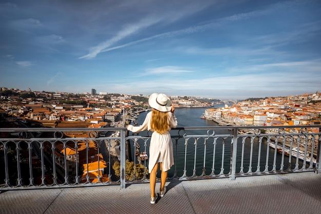 Jeune femme touriste bénéficiant d'une vue magnifique sur la vieille ville et le fleuve douro debout sur le pont de fer par temps ensoleillé dans la ville de porto, portugal