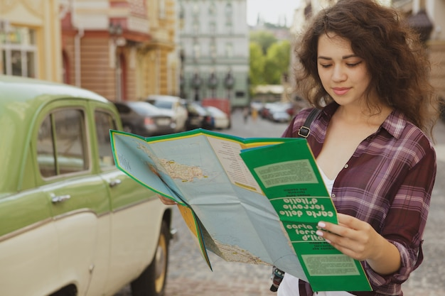 Jeune femme touriste examinant une carte, voyageant en été, espace copie