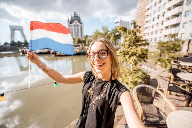 Jeune femme touriste faisant une photo de selfie avec un drapeau néerlandais debout dans le vieux port de la ville de rotterdam