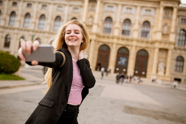 Jeune femme touriste prenant selfie avec photo mobile dans la rue dans le centre de vienne, autriche