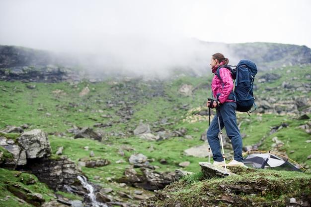 Jeune femme touriste avec sac à dos debout au sommet d'un rocher, profitant d'un paysage de montagne fantastique autour