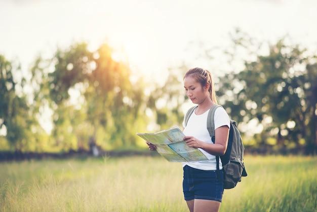 Jeune femme touriste tenant la carte en voyage