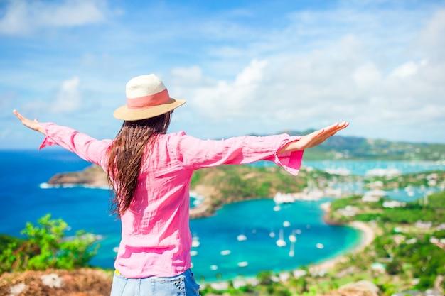 Jeune femme touriste avec vue sur le port anglais de shirley heights, antigua, paradis bay sur une île tropicale dans la mer des caraïbes