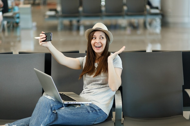 Jeune femme touristique amusante travaillant sur un ordinateur portable, faisant du selfie sur un téléphone portable, écartant les mains, attendant dans le hall de l'aéroport