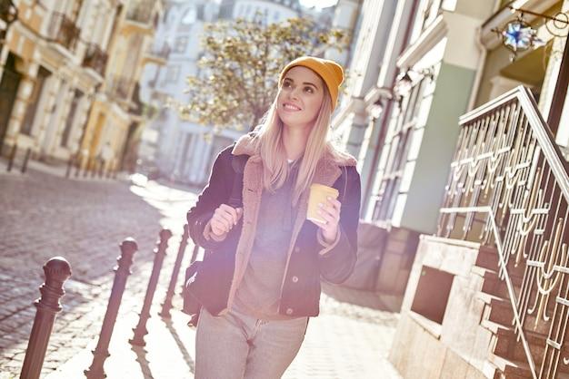 Jeune femme touristique attirante boit du café dans la rue