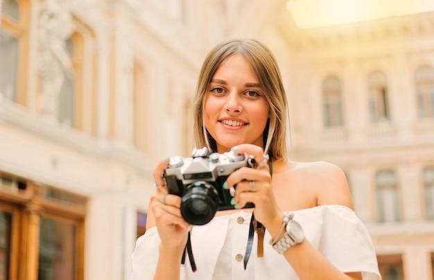 Jeune femme touristique dans des vêtements à la mode avec appareil photo rétro