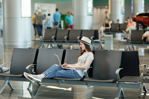 Jeune femme touristique détendue au chapeau travaillant sur un ordinateur portable en attendant dans le hall de l'aéroport international