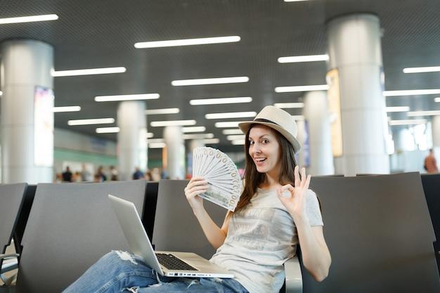 Jeune femme touristique avec ordinateur portable tenant un paquet de dollars, de l'argent en espèces, montrant un signe ok, attendant dans le hall de l'aéroport