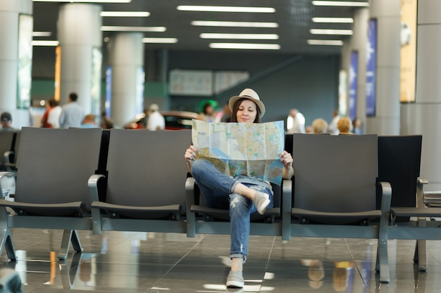 Jeune femme touristique souriante tenant une carte papier, cherchant un itinéraire en attente dans le hall du hall de l'aéroport international