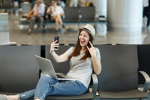 Jeune femme touristique voyageur travaillant sur un ordinateur portable faisant un selfie sur un téléphone portable, montrant un panneau rock-n-roll en attente dans le hall de l'aéroport