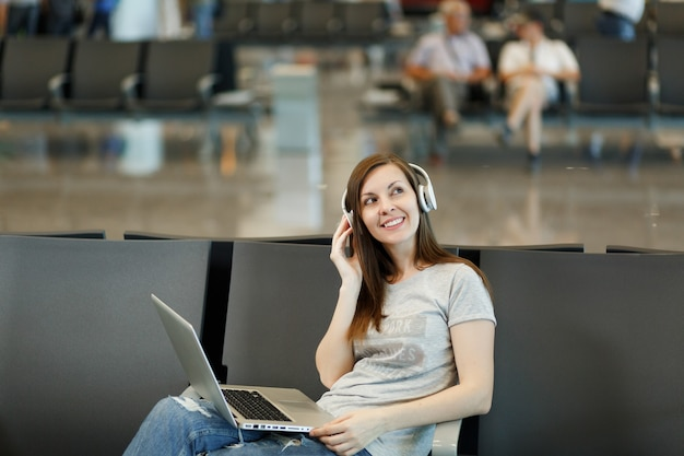 Jeune femme touristique voyageuse pensive avec des écouteurs écoutant de la musique travaillant sur un ordinateur portable, attendez dans le hall de l'aéroport international