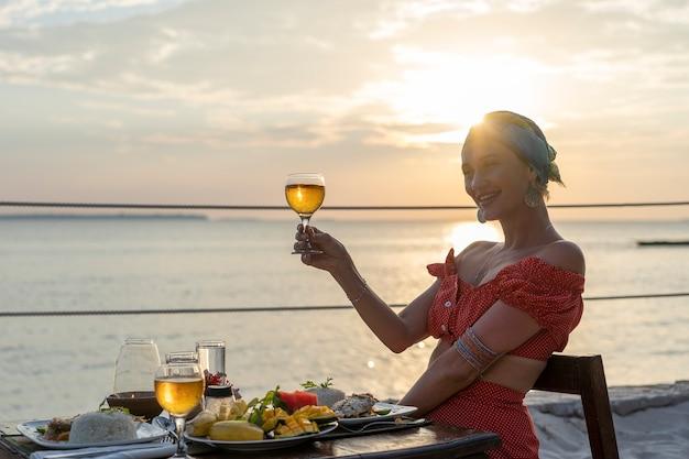 Jeune femme en train de dîner romantique au restaurant de l'hôtel pendant le coucher du soleil près des vagues de la mer sur la plage tropicale, gros plan. la fille profite du coucher de soleil avec un verre de vin. concept de loisirs et de voyage