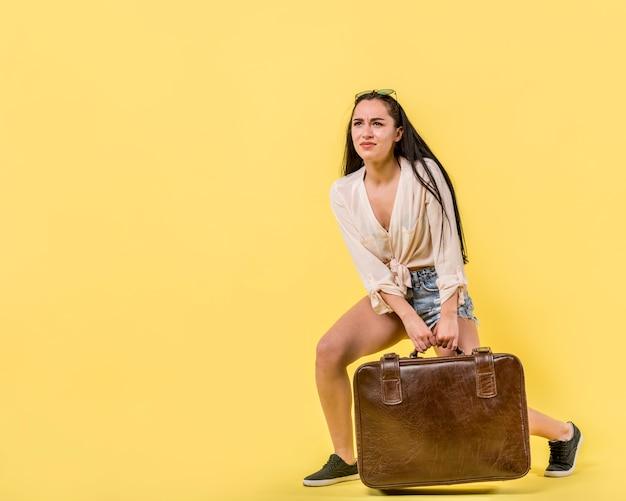 Jeune femme traînant une valise vintage