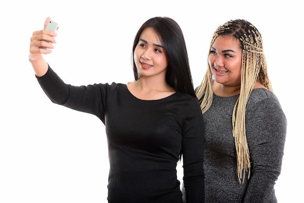 Jeune femme transgenre asiatique heureuse et femme asiatique souriant