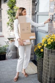 Jeune femme transportant des colis à la maison, debout avec un tas de cartons sur le porche de sa maison. concept d'achat de marchandises en ligne et de livraison à domicile