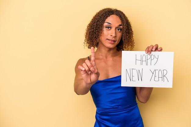 Jeune femme transsexuelle latine célébrant le nouvel an isolé sur fond jaune montrant le numéro un avec le doigt.