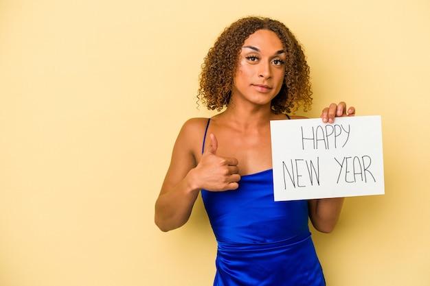 Jeune femme transsexuelle latine célébrant le nouvel an isolé sur fond jaune souriant et levant le pouce vers le haut