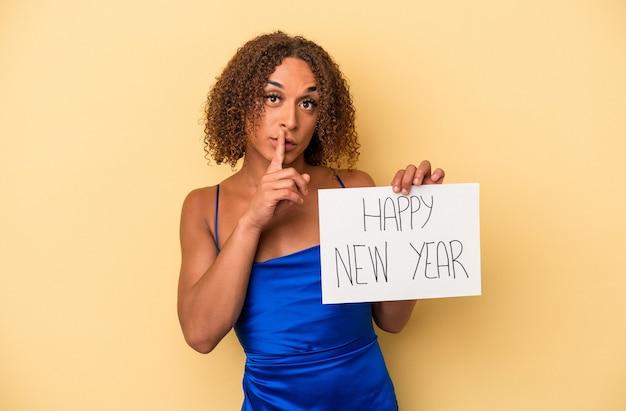 Jeune femme transsexuelle latine célébrant le nouvel an isolée sur fond jaune gardant un secret ou demandant le silence.